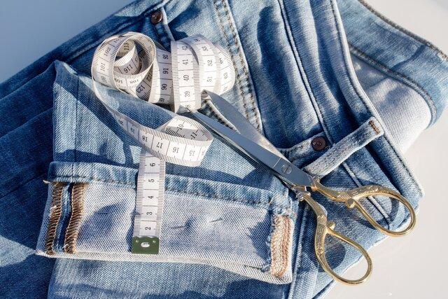 Calça jeans, fita métrica e tesoura
